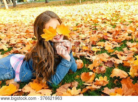Autumn Portrait Of Happy Smiling Little Girl Child Lying In Leaves And Closing Her Eyes With Leaves