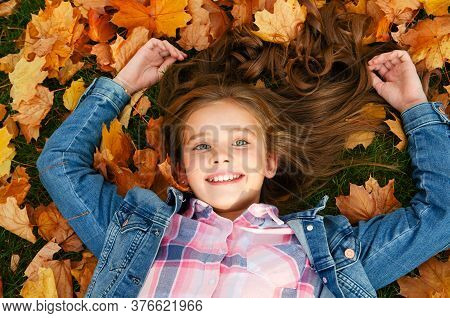 Autumn Portrait Of Happy Smiling Little Girl Child Lying In Leaves In The Park Outdoors