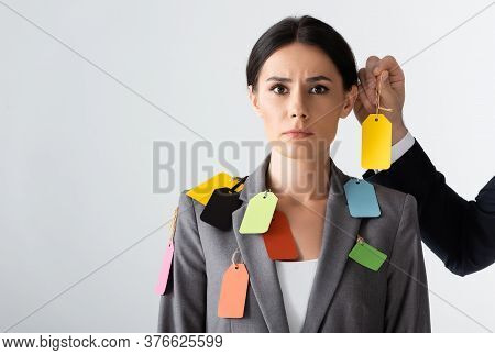 Businessman Putting Label On Beautiful Businesswoman Isolated On White, Gender Inequality Concept
