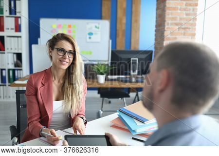 Portrait Of Two People Involved In Talk. Man And Woman Discuss Working Situation. Modern Tablet With