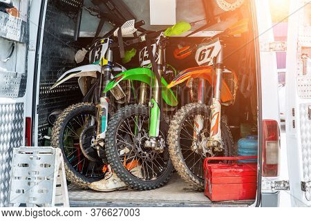 Three Bright Dirty Sport Motocross Motorcycles Stand In Tail Of Technical Support Assistance Van In