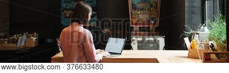 Back view of brunette woman sitting by the table and using laptop computer over wall on background with inscription if these wall could talk
