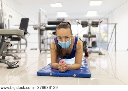 Woman have indoor training with push-ups in gim with medical facemask. Female breathes deeply stock photo