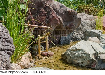 Bamboo Sound Water Fountain Next To Calm Languid Stream Surrounded Natural Stones As Part Of Traditi