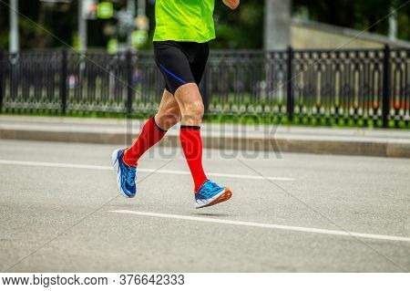 Legs Male Runner In Bright Red Compression Socks Run Down Street Race