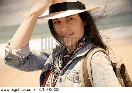 Portrait of 40-year-old woman with dark hair, wearing hat and standing on the beach