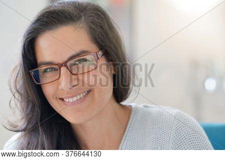 Portrait of beautiful 40-year-old woman with long dark hair wearing eyeglasses