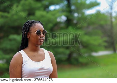 A Portrait Of A Beautiful African-american Teenaged Girl Standing Alone Outside And Feeling Sad And