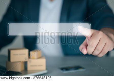Businessman With Index Finger Clicks On Search Bar With Miniatur Brown Box Background. Idea For Sear