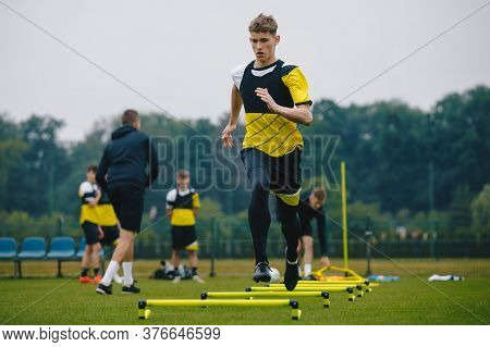 Teenager Boy Soccer Player In Training. Young Soccer Players At Practice Session With Coach. Footbal