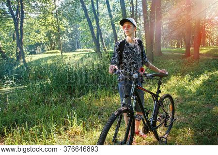 A Tourist Biker Is Sitting On A Bicycle. Biker Stopped In A City Park Against The Backdrop Of The Se