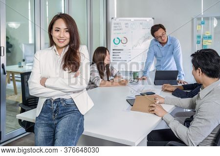 Portrait Of Asian Business Woman With Arms Crossed And Standing Over The Group Of Colleague Partner