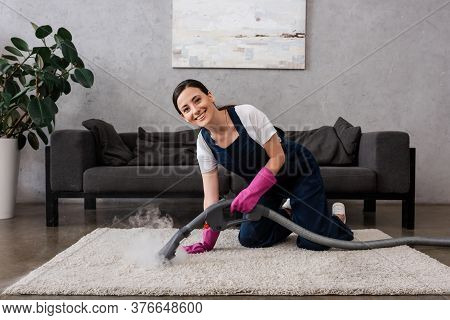 Cleaner Smiling At Camera While Using Vacuum Cleaner With Hot Steam On Carpet In Living Room