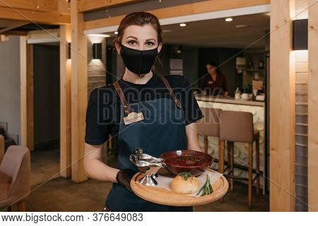 A Pretty Waitress Who Wears A Black Face Mask And Disposable Gloves Is Holding Ukrainian Borsch With