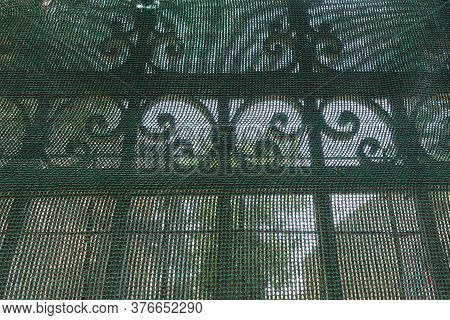 Wrought Iron Antique Fence Railings Behind Transparent Debris Netting.