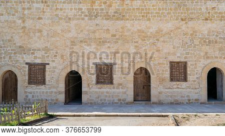 Four Weathered Wooden Arched Doors And Three Closed Rusted Wrought Iron Window On Bricks Stone Wall
