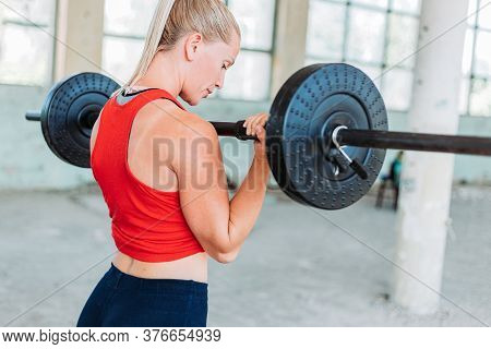 Fit Blond Woman Weight Lifting In Red Sportswear. Training, Active Lifestyle. Arms Workout. Back Vie