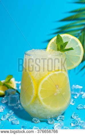 Lemonade Frappe With Round Slice Of Lemon And Mint On Blue Ice Background. Mojito Frappe In Glass Wi