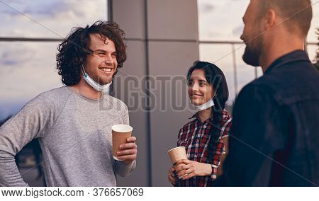 Happy Man With Medical Mask And Drink To Go Talking With Male And Female Coworkers While Standing Ou