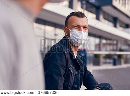 Young Guy In Medical Mask Talking With Friend While Resting On City Street During Coronavirus Epidem