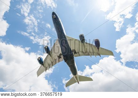 the sun behind a large passenger jet on landing approach to an airport with its undercarriage down