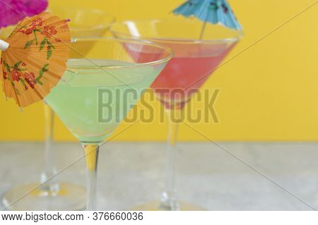 Glasses Of Various Delicious Fruit Non-alcoholic Cocktails On A Bright Background With Umbrellas. He