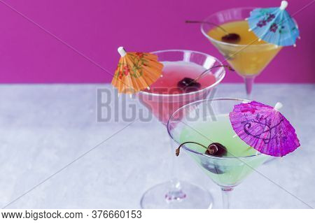 Glasses Of Various Delicious Fruit Non-alcoholic Cocktails On A Bright Background With Umbrellas And