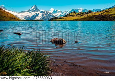 Picturesque View Of Mountain Lake Bachalpsee With The Snow Capped Peaks Of Wetterhorn, Schreckhorn A