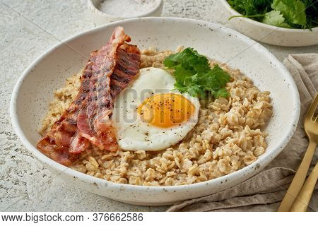 Oatmeal, Fried Egg, Fried Bacon. Hearty Fat High-calorie Breakfast. Balance Of Proteins, Fats, Carbo