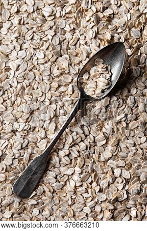 Metal Spoon With Few Flakes Of Rolled Oats In It. Spoon Is On Layer Of Rolled Oats. Source Of Vegeta