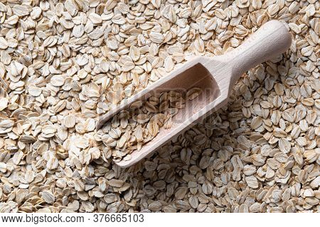 Wooden Scoop With Few Flakes Of Dry Rolled Oats In It. Scoop Is On Layer Of Raw Rolled Oats. Source