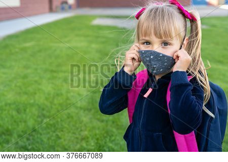 Young Student Caucasian Girl Looking At Camera And Wear Protective Face Mask Before School Day. Read