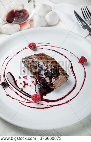Venison Meat With Raspberry Sauce On A White Plate. On A White Wooden Table.