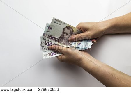 Female Hands Holds A Five Thousand Hryvnia. Ukrainian Currency With Woman's Hands Against A White Ba