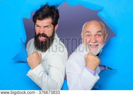 Men Making Hole In Paper. Emotions. Successful Men Look Through Hole In Paper. Bearded Men Peeking F