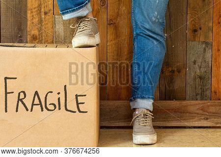 Moving Box With The Word Fragile Near Wooden Wall, Two Legs With Jeans And Sneakers In Retro Room Ne