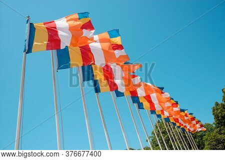 Row Of Buddhist Flags Fluttering On Blue Sky