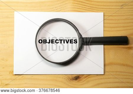 Magnifying Glass With Text Objectives On Wooden Table.