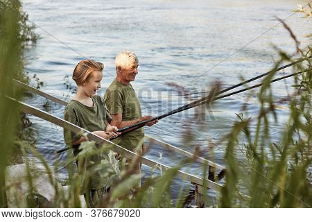 Fishing By Lake, Grandson And Grandfather Near River, Holding Fishing Rods In Hands, Look Excited An
