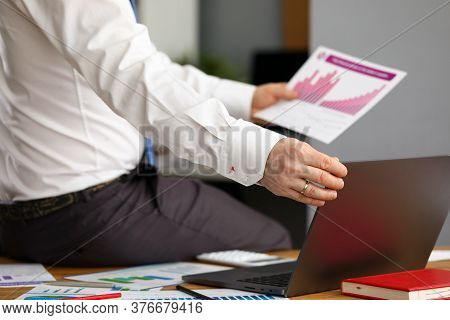 Close-up Of Executive Manager Sitting On Table In Office. Male Person Working On Laptop. Businessman