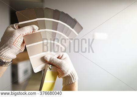Close-up Of Person Decorator Holding Colour Palette Samples. Examples With Wall Or Floor Paintings.