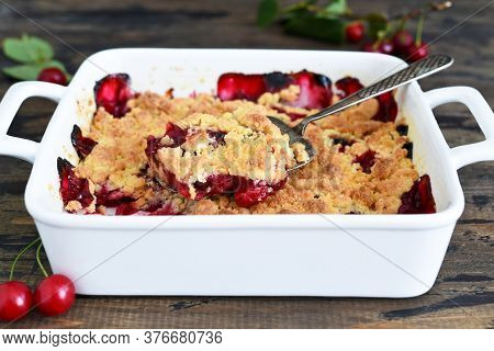 Homemade Summer Dessert With Cherries. Crumble With Cherries In A Baking Dish On A Wooden Background
