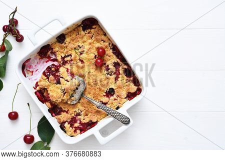 Homemade Summer Dessert With Cherries. Crumble With Cherries In A Baking Dish On A White Background.