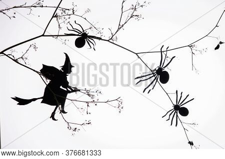 Black Paper Silhouette Of A Witch Flying To Sabbath On Halloween Night, On White Background. Homeman
