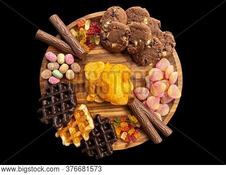Different Sweet And Delicious Candies On A Wooden Plate On A Black Background With Chips, Cockies, G