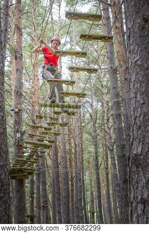 Woman Crossing A Tibetan Bridge In An Adventure Park In A Pine Forest Vertical