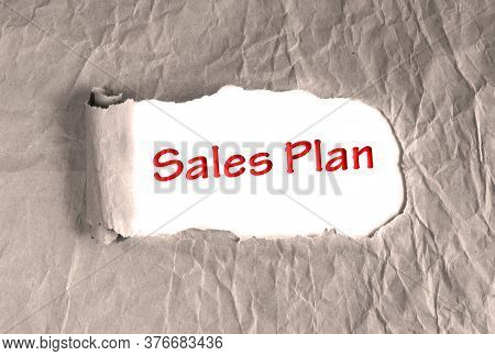 Words Sales Plan On Torn Brown Grunge Paper Background. Marketing Strategy, Different Trajectories I