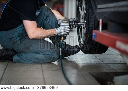 Car mechanic changing tires of a car in a repair shop/car garage (shallow DOF/color toned image)