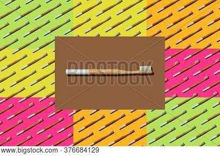 Bamboo Toothbrush With A White Bristles In Brown Rectangle Over Multicolor Toothbrushes Pattern. Zer