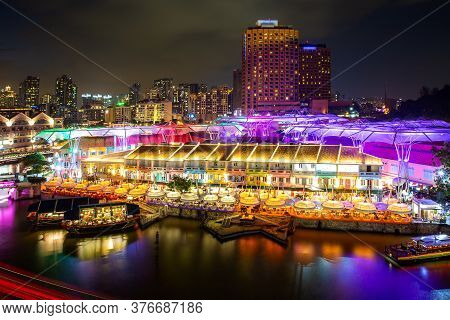 Colorful Light Building At Night In Clarke Quay Market With River At Singapore. Asian Tourism, Moder